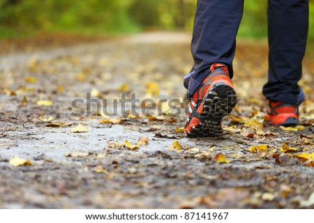 man walking cross country and trail in autumn forest - stock photo
