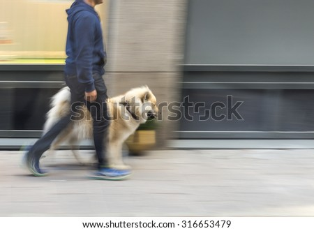 Man walking dog on street in blurred motion - stock photo