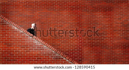 Man walking down stairs with brick wall in background