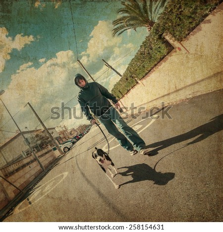 Man walking his dog down the street - stock photo