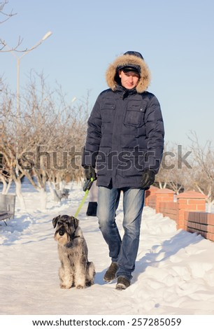 Man walking his dog on a snowy path in winter posing for the camera with the schnauzer sitting at his feet in the sunshine - stock photo