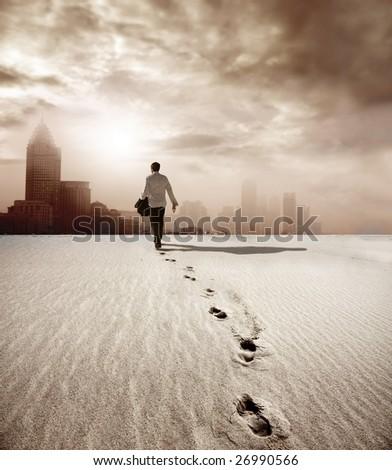 man walking in a desert towards a city - stock photo