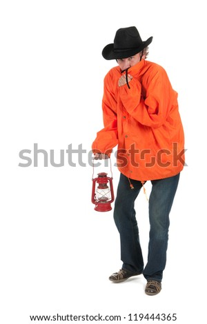 Man walking in bad weather with oil lamp - stock photo