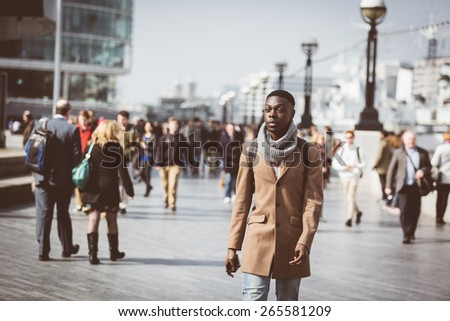 Man walking in London on Thames sidewalk, with blurred people on background. He is looking away. Photo taken on a sunny winter day. Vintage filter applied. - stock photo