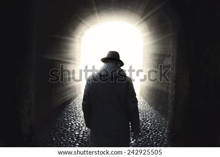 Man walking into light  - stock photo