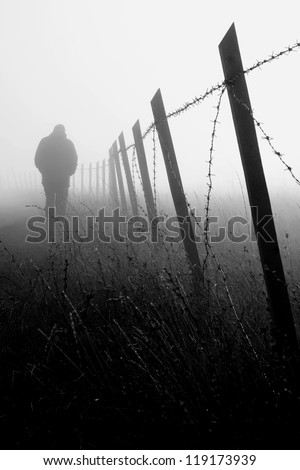 Man walking near barbed wire fence in dense fog - stock photo