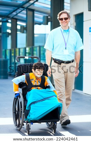 Man walking next to little boy in wheelchair outside medical facility - stock photo