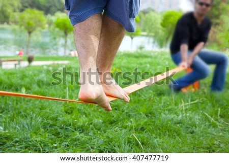 Man walking on a rope in the park in summer. Slacklining. - stock photo