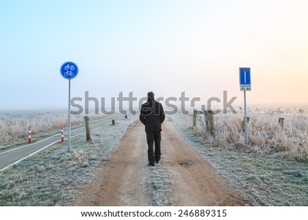 Man walking on a sand road in a winter landscape in the Netherlands - stock photo