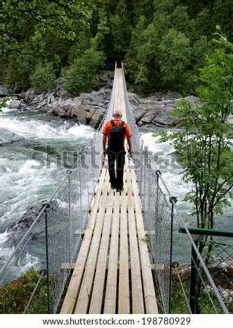 Man walking on a suspension bridge - stock photo