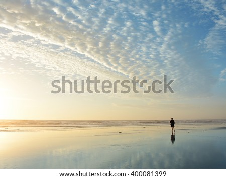 Man walking on beach at sunrise, beautiful cloudy sky reflected on the beach, Jacksonville, Florida, USA. - stock photo