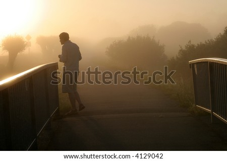 man walking on bridge in misty countryside