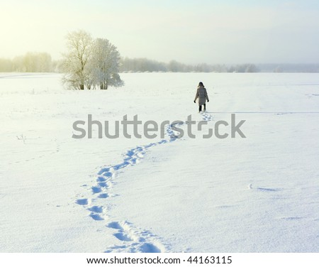 Man walking on deep snowy field - stock photo
