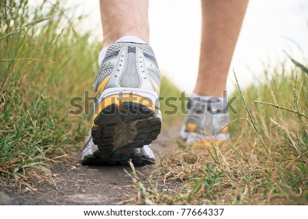 Man walking on footpath, sports shoe closeup, exercise outdoors. Running or jogging outside in summer nature, fitness and health concept - stock photo