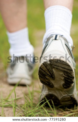 Man walking on hiking trail in forest, sport shoe closeup - stock photo