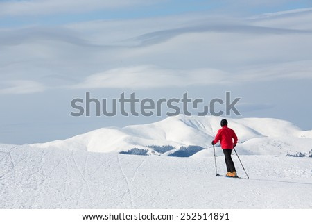 Man walking on ski in mountain with white clouds - stock photo