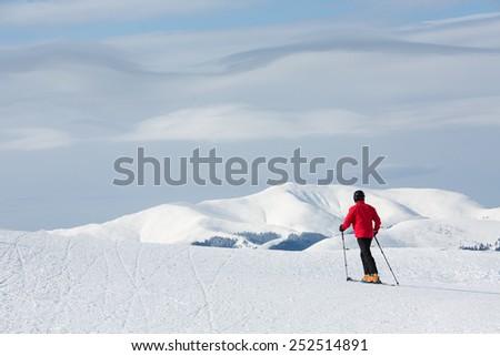Man walking on ski in mountain with white clouds - stock photo