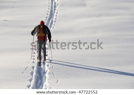 Man walking on ski in the snow - stock photo