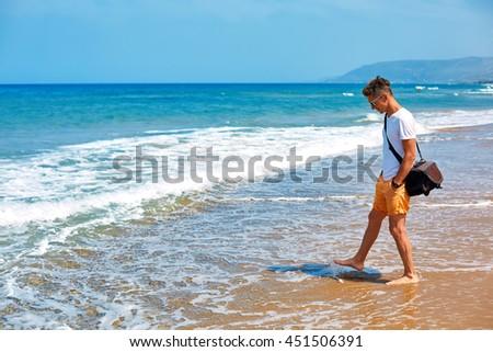 man walking on the empty sunny beach, Crete, Greece - stock photo