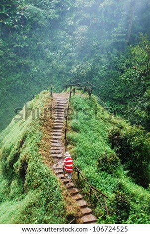 Man walking on the green hill slope - stock photo