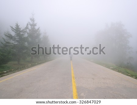 man walking on the road in fog - stock photo