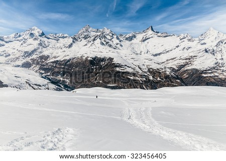 Man walking on the snow with the background of snow mountain. - stock photo