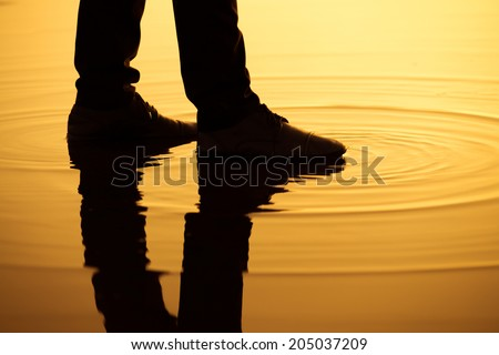 Man walking on the water surface with silhouette legs reflection. - stock photo