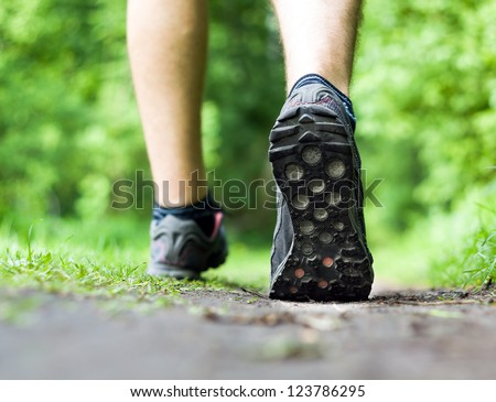 Man walking or running on trail in forest summer nature outdoors, sport shoes and exercising on footpath - stock photo