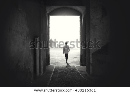 Man walking out from a dark alley - stock photo
