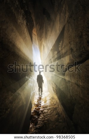 man walking out of a cave - stock photo