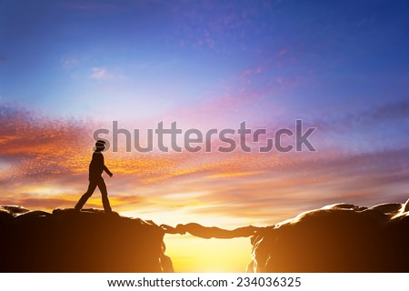 Man walking over precipice between two mountains, another man serving as a bridge. Sunset, business conceptual - stock photo