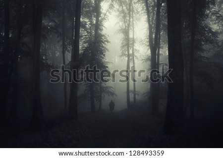 man walking through a dark spooky forest - stock photo