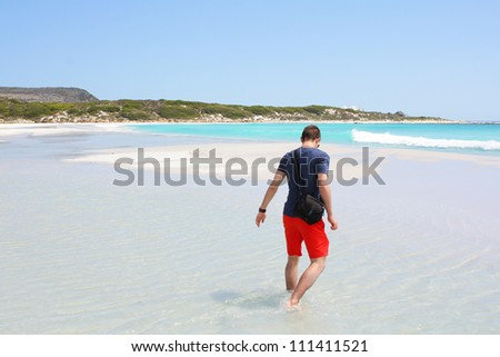 Man walking through water at Kommetjie Beach, Cape Town, South Africa - stock photo