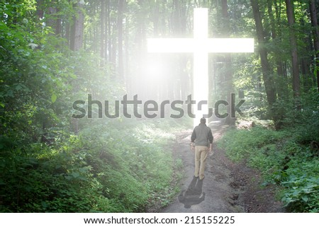 Man walking to a Christian Cross of Light