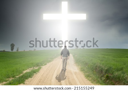Man walking to a Christian Cross of Light - stock photo