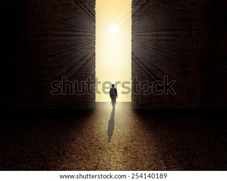Man walking towards the light from darkness