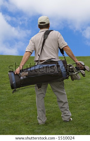 Man walking up hill carry bag of golf clubs. - stock photo