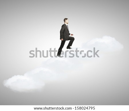 man walking  up stairs out of clouds - stock photo