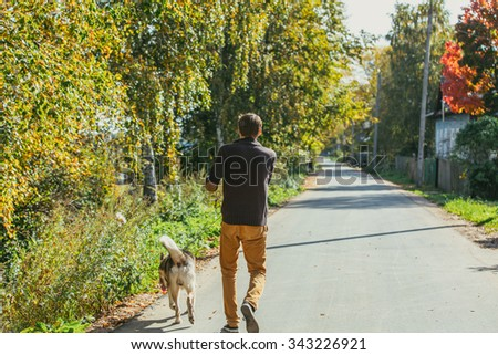 Man walking with a hunting dog - the West Siberian husky.  Back view. Panorama. Those men are not seen. Autumn. Copy space. - stock photo