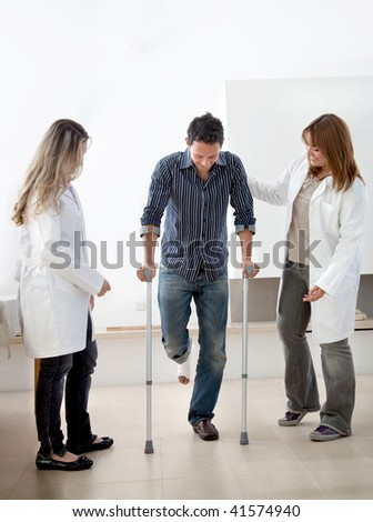 Man walking with crutches at a hospital with doctors