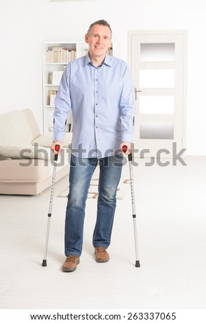 Man walking with crutches, rehabilitation after injury - stock photo