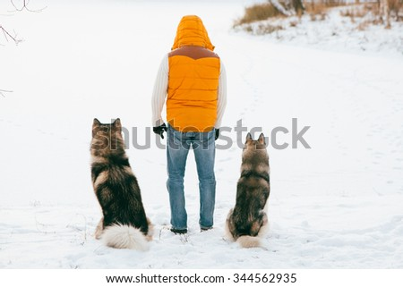 Man walking with dog winter back view  - stock photo