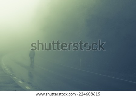 Man walks into foggy road  - stock photo
