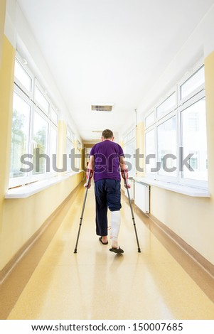 Man walks on crutches after arthroscopic surgery - stock photo