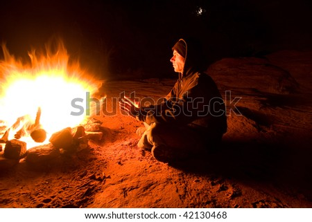 Man warming himself in front of blazing campfire on a cold night of camping. Full moon showing through tree branches in background. - stock photo