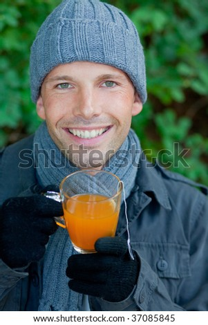 Man warming up with hot tea in cold autumn winter time sitting on a bank in a green fall parc - stock photo
