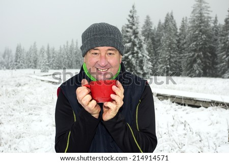 Man warms up a hot drink in the cup - stock photo