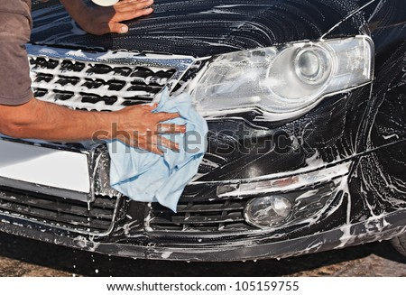 Man washing a black car with a cloth - stock photo