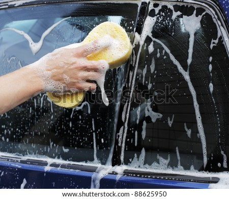 Man washing a car with a yellow sponge. - stock photo