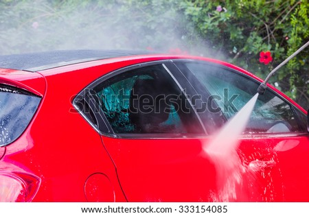 Man washing a red car